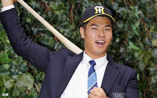 阪神入団が決まり、ポーズをとる近大の佐藤輝明内野手(12日、大阪市)=共同