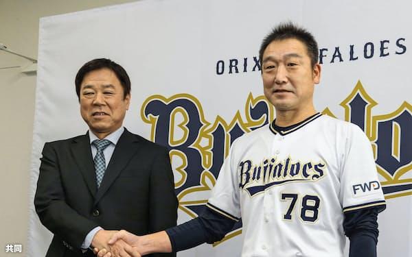来季監督就任が発表され、福良淳一GM(左)と握手するオリックスの中嶋聡監督代行(12日、大阪市)=共同