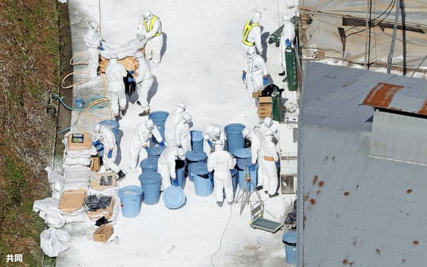 今季3例目の鳥インフルエンザが確認された香川県三豊市の養鶏場で、防護服を着用し作業する人たち(11日)=共同
