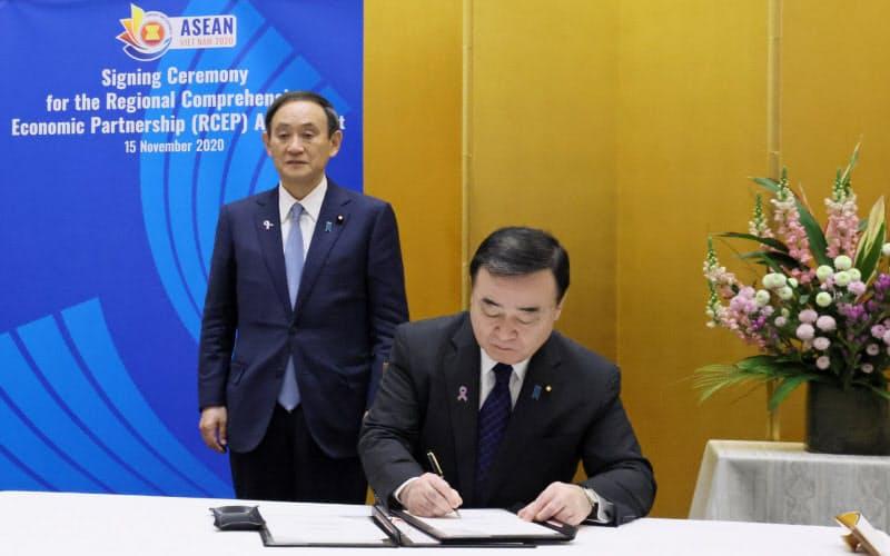 RCEPの協定に署名する梶山経産相(右)と首相(内閣広報室提供)