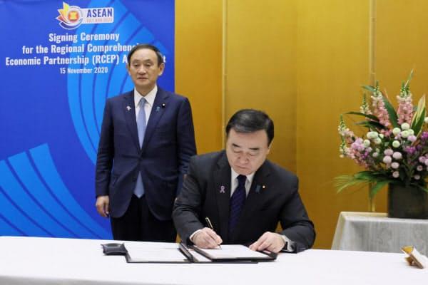RCEPの協定に署名する梶山経産相(右)と菅首相(内閣広報室提供)