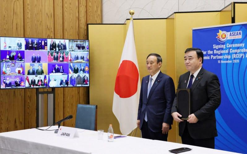 RCEP首脳会議にテレビ会議形式で出席した首相(左)と梶山経産相(内閣広報室提供)
