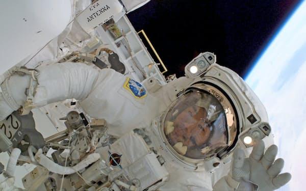 スペースシャトルに搭乗した際の船外活動で船内のクルーに手を振る野口さん(2005年8月)=JAXA・NASA提供