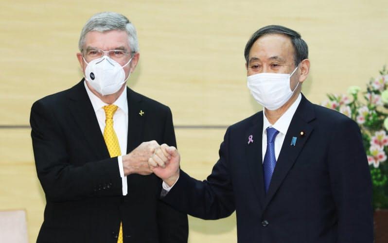 会談を前に拳を合わせる菅首相とIOCのバッハ会長(16日午前、首相官邸)