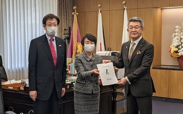 指定都市市長会の林会長(横浜市長、写真中央)は「特別自治市」の早期実現を求める提言・要請を武田総務相(写真右)に手渡した(16日)