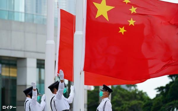 香港市民に愛国心を持つように促す動きも強まっている(10月1日、香港で開かれた国慶節の行事で中国国旗を掲揚する香港警察の要員)=ロイター
