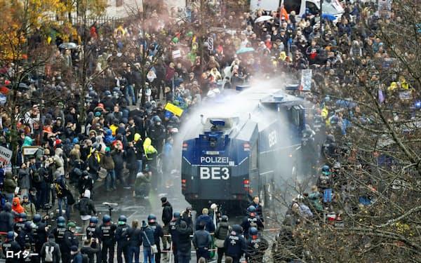 18日、ベルリンで、極右や市民らのデモに放水する警察車両=ロイター