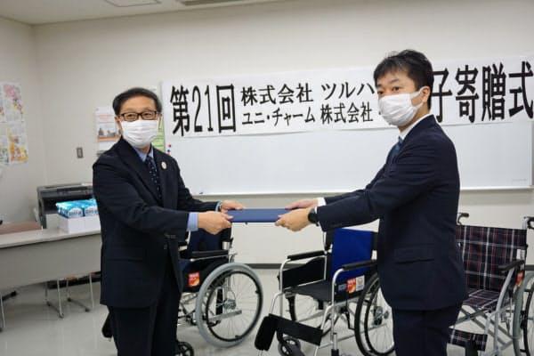車椅子とマスクを寄贈するツルハHDの鶴羽順社長(右)