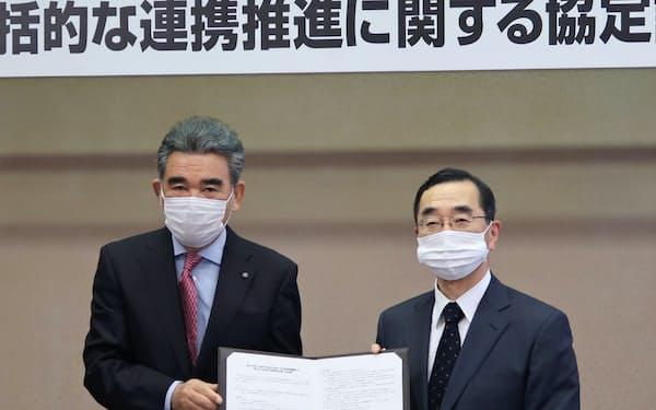 協定に調印した越智学長(左)と佐々木理事長