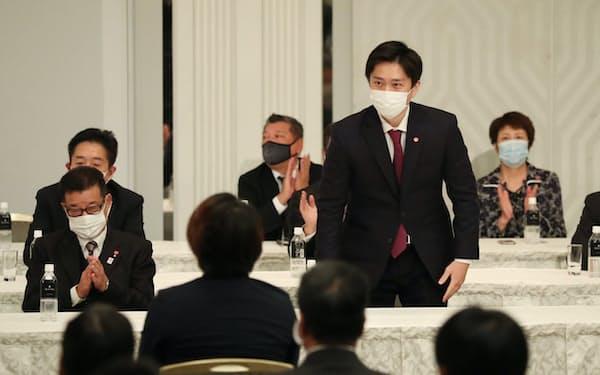 大阪維新の会の新代表に選出され、一礼する吉村大阪府知事。左は松井大阪市長(21日、大阪市中央区)