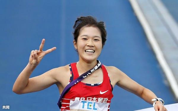 2年連続3度目の優勝を決め、笑顔でゴールする日本郵政グループのアンカー・大西ひかり(22日、弘進ゴムアスリートパーク仙台)=共同