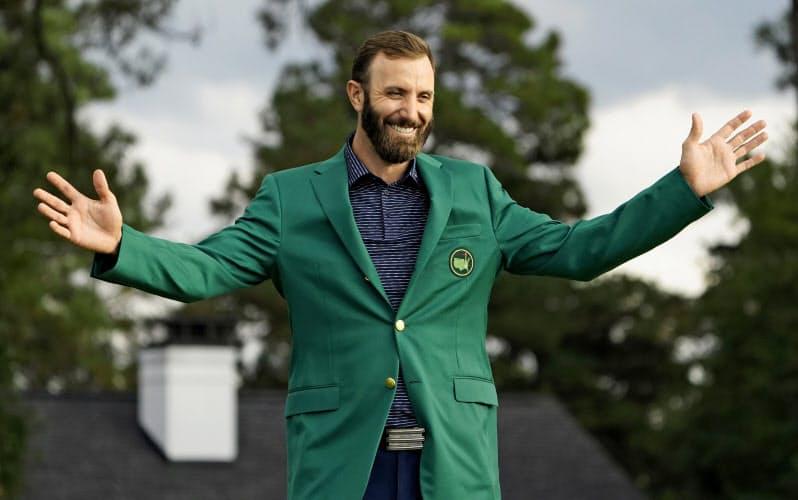 初めてグリーンジャケットに袖を通し笑顔のD・ジョンソン。来年の東京五輪は出場辞退を決めている=AP