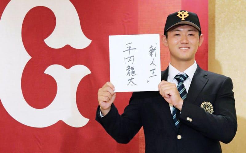 巨人にドラフト1位で入団することが決まり、「新人王」と書いた色紙を手に笑顔の平内龍太投手(23日、東京都内のホテル)=共同