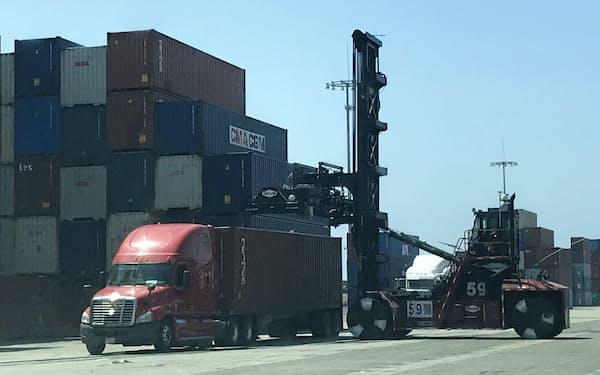 コンテナを運ぶ大型運搬機「トップハンドラー」(右)は大量の石油燃料を消費する(米カリフォルニア州ロサンゼルス港)