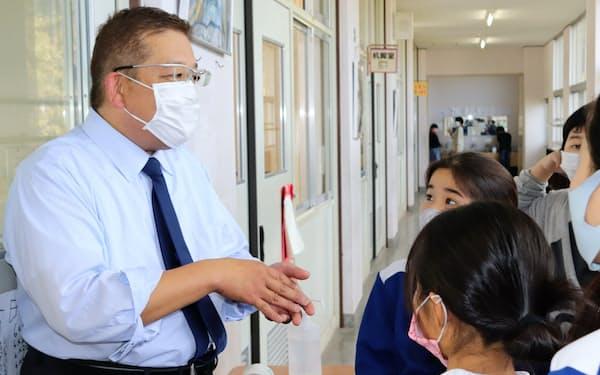廊下で児童と話す鈴木伸昭さん(11月中旬、北九州市立到津小学校)