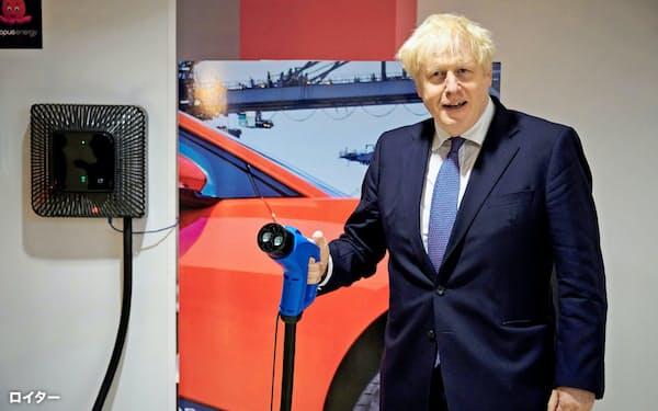 英国など主要国は脱ガソリン車を加速(10月5日、充電装置を持つジョンソン英首相)=ロイター