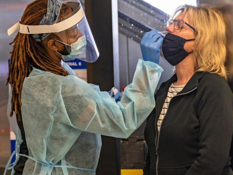 米国では感染拡大に歯止めがかからない(25日、ロサンゼルス国際空港)=AP