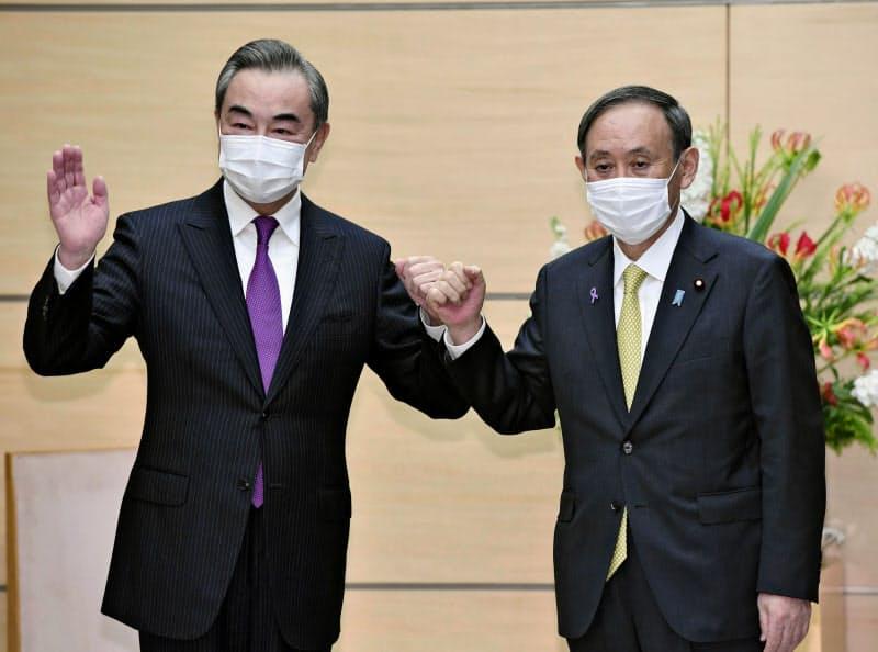 会談前、グータッチを交わす中国の王毅国務委員兼外相(左)と菅首相=25日午後、首相官邸