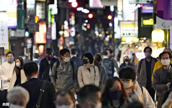 東京・新橋の繁華街をマスク姿で歩く人たち(26日夜)=共同