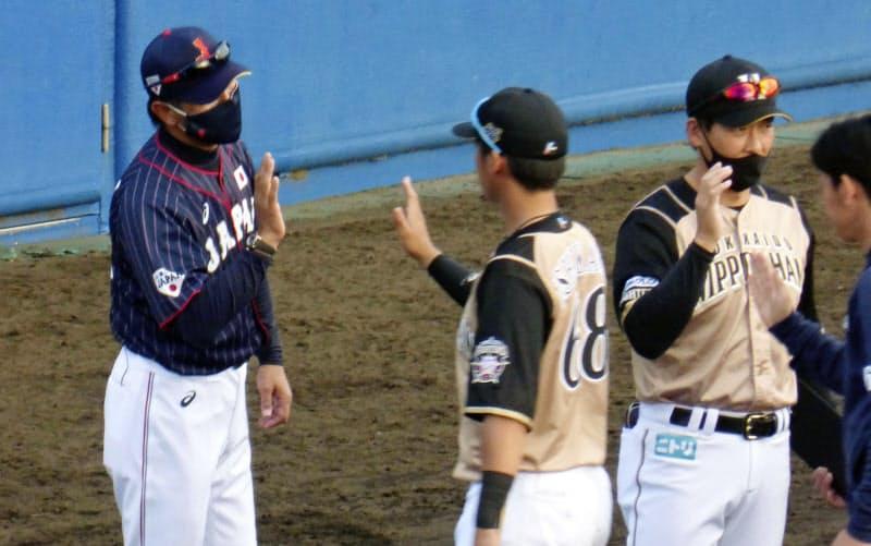 秋季教育リーグで日本ハムを率いた日本代表の稲葉監督=左(26日、宮崎県日南市)=共同