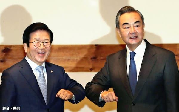 会談に先立ち中国の王毅国務委員兼外相(右)とあいさつを交わす韓国国会の朴炳錫議長(27日、ソウル)=聯合・共同
