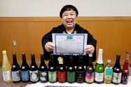 Non-GMO証明書を手にする久慈社長と認証を取得した日本酒や果実酒