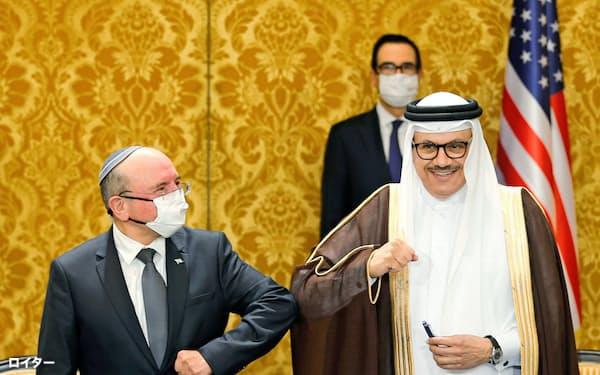 合意文書に署名後、ひじをぶつけて友好をアピールするイスラエルとバーレーンの代表者(マナマ)=ロイター