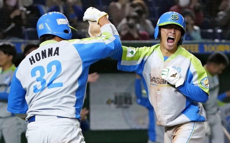 三菱自動車倉敷―セガサミーの3回裏、小野田の2点二塁打で生還し、三走本間(左)とタッチを交わす一走大内(27日、東京ドーム)=共同