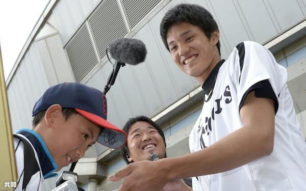 サインはファンと選手をつなぐ大切なものだ(2013年2月、春季キャンプで男の子にサインを手渡す阪神・藤浪)=共同