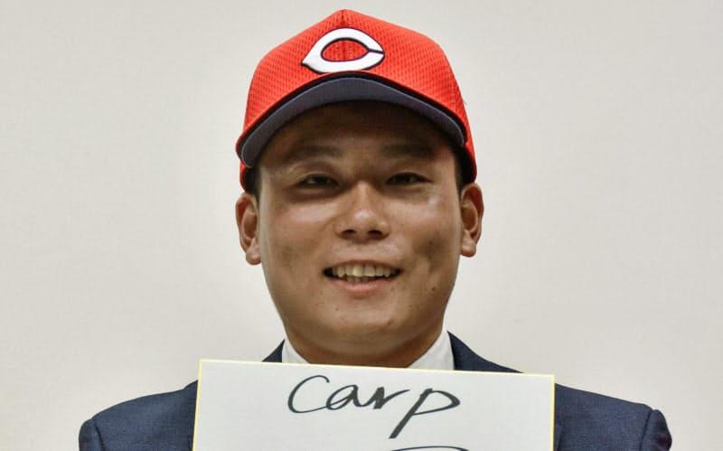 広島との入団交渉を終え、色紙を手にするトヨタ自動車の栗林良吏投手(30日、名古屋市)=共同