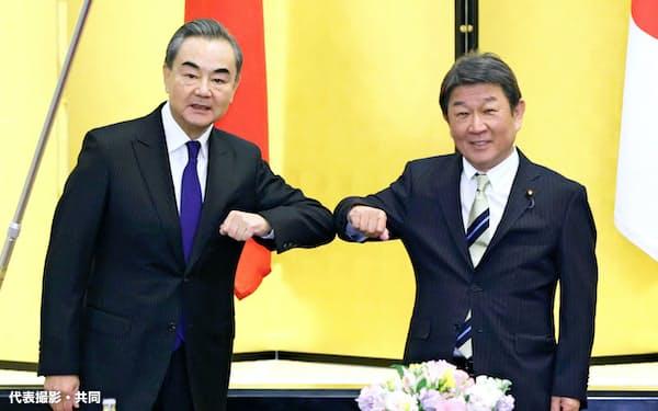 会談を前に肘タッチを交わす中国の王毅国務委員兼外相(左)と茂木外相(11月24日午後、東京都港区の飯倉公館)=代表撮影・共同