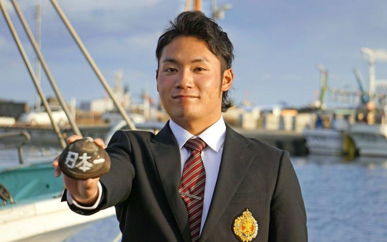 入団が決まり、北海道・苫小牧漁港でポーズをとる日本ハムドラフト1位の伊藤大海投手(1日)=共同
