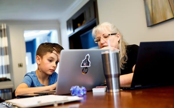 ワーキングマザーへの負荷は高まっている(米ワシントン州で働く母親の代わりに祖母から支援を受けてオンライン授業の準備をする少年)=ロイター