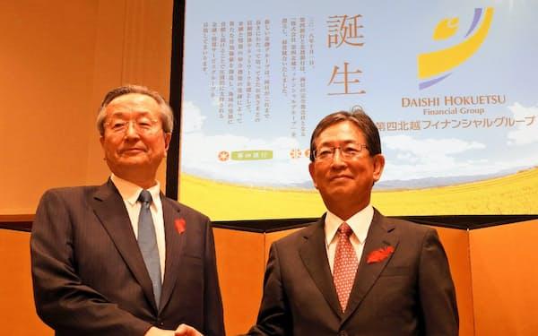 経営統合を発表する第四北越フィナンシャルグループの佐藤勝弥会長(右)と並木富士雄社長(2018年、新潟市)