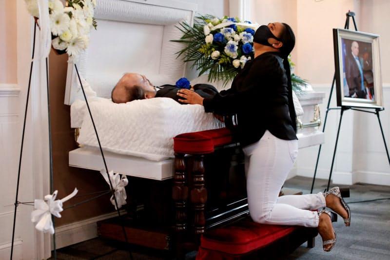 新型コロナの感染で亡くなったパートナーの葬儀でひざまずく女性(5月、ニューヨーク)=ロイター