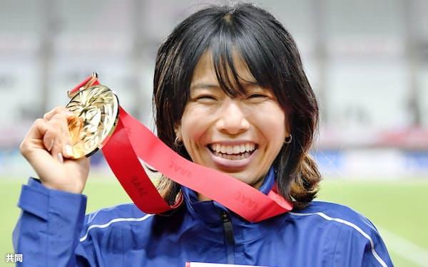 女子1万メートルを日本新記録で制し、メダルを手に笑顔を見せる新谷仁美(4日、ヤンマースタジアム長居)=共同