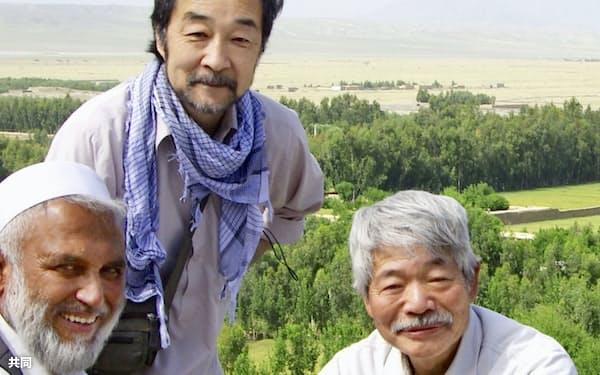 アフガニスタンで中村哲さん(右)と写真に納まる谷津賢二さん(上)(2019年4月、谷津賢二さん提供)=共同