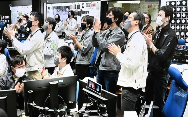 投下したカプセルが大気圏に突入したことを確認し、管制室で喜ぶJAXAのスタッフら(6日未明、神奈川県相模原市)=モニター画面より