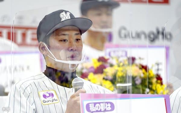 ロッテの新入団選手発表で、将来の目標を書いた色紙を手にする鈴木昭汰投手(9日、さいたま市)=共同