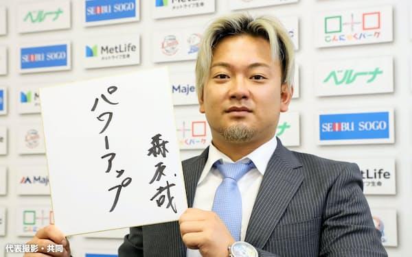 契約更改交渉を終え、来季の目標を記した色紙を手にする西武・森(9日、埼玉県所沢市の球団事務所)=代表撮影・共同