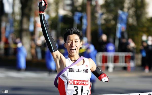 12年ぶり3度目の優勝を決め、指を突き上げる富士通のアンカー・浦野雄平(1日、群馬県庁前)=共同