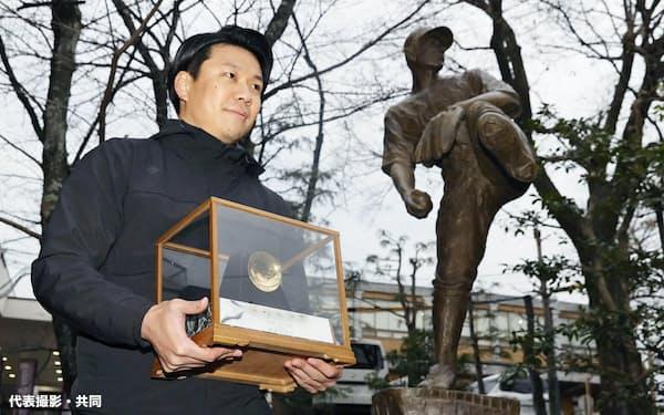 沢村賞の金杯を手に、故沢村栄治氏の銅像の前に立つ中日の大野雄(5日、京都市の京都学園高)=代表撮影・共同