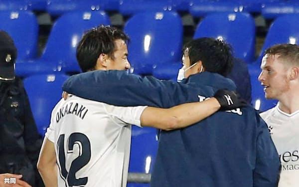 試合終了後、ウエスカの岡崎(左)と肩を組むヘタフェの久保建(20日、ヘタフェ)=共同