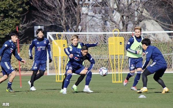 J1横浜Mの今季初練習でボールを奪い合う喜田=中央手前=と仲川=同奥(25日、横浜市)=共同