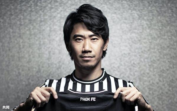名前入りのPAOKのユニホームを手にする香川真司(26日)=共同