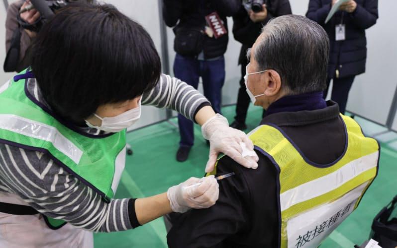 新型コロナワクチンの接種会場運営訓練で、被接種役の男性に注射を打つ看護師(27日、川崎市幸区)