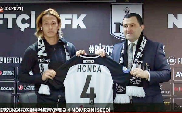 アゼルバイジャン・プレミアリーグのネフチに加入が決まり、記者会見で背番号4のユニホームを手にする本田圭佑=左(15日)=同クラブ公式YouTube提供・共同