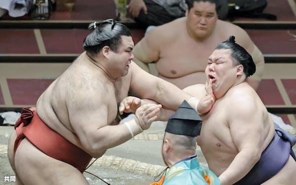 阿武咲(右)を攻める高安。はたき込みで下す(22日、両国国技館)=共同