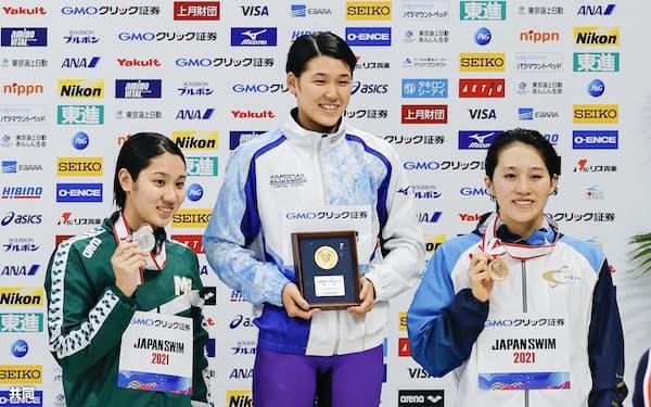 女子400メートル自由形の表彰式で笑顔を見せる(左から)2位の難波実夢、優勝した小堀倭加、3位の佐藤千夏(4日、東京アクアティクスセンター)=共同