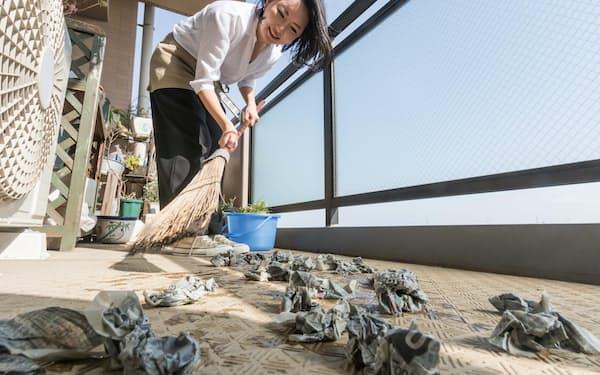 ぬらした新聞紙をまいてから掃き掃除をする=高井 潤撮影